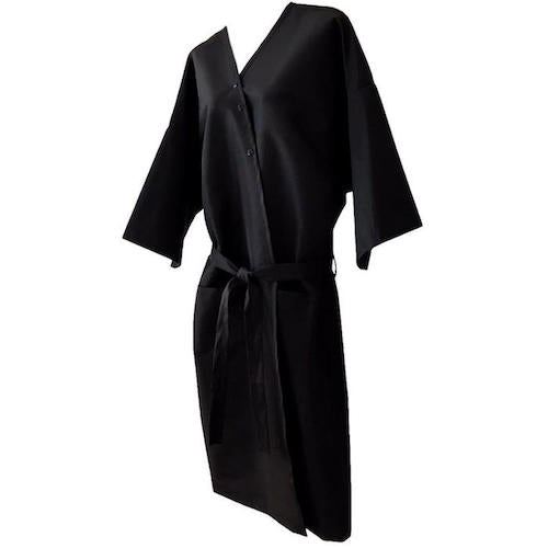 Black, kimono-style client wrap/robe/gown. Product closes in the front with three stainless steel snaps and a long attached belt for complete coverage. The wraps come in two sizes; Regular & XL, both sizes have two deep pockets, and ¾ length sleeves. The fabric is nylon/polyester making the product water repellent, stain resistant, and washer and dryer safe.  Side view of the product.
