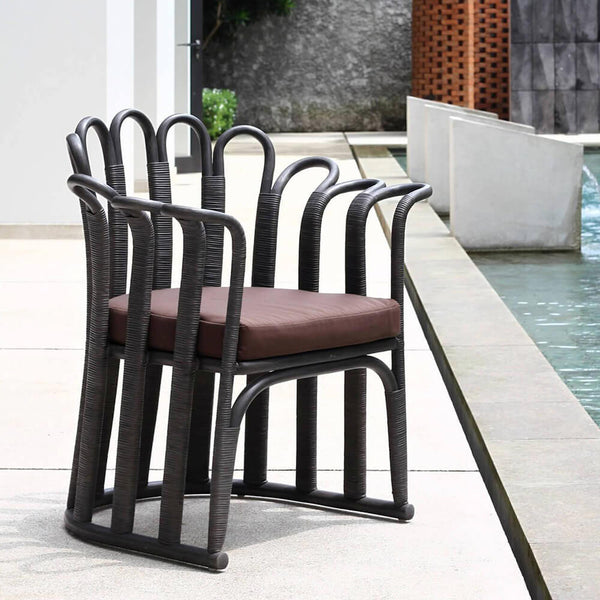 Black outdoor dining chair with maroon cushion. made from curved corolla, aluminum and synthetic rattan.