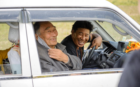 Two Tibetan men laugh while taking a break in their car.