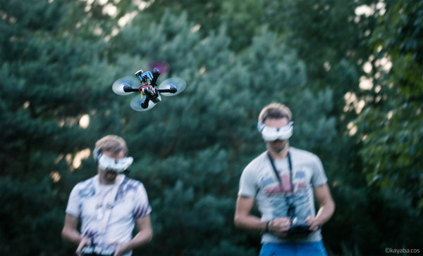 Two men in FPV goggles flying FPV quadcopter