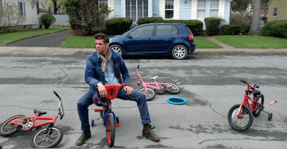 artist joseph ferm on kids bicycle in street
