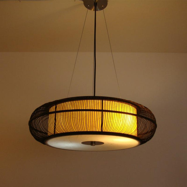 Caged circular pendant light in black or beige