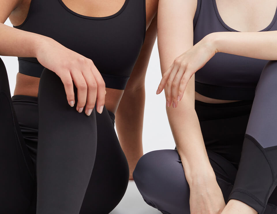 Upclose of two women sitting next to eachother sporting tenrees Active Wear.