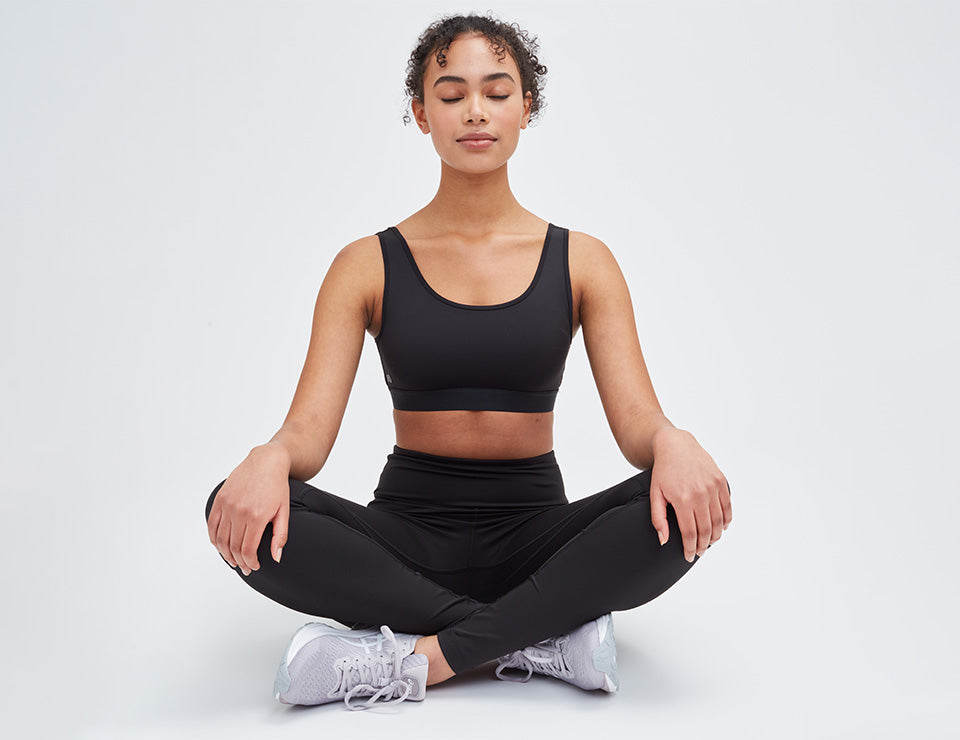 Woman sitting cross legged with her eyes closed.