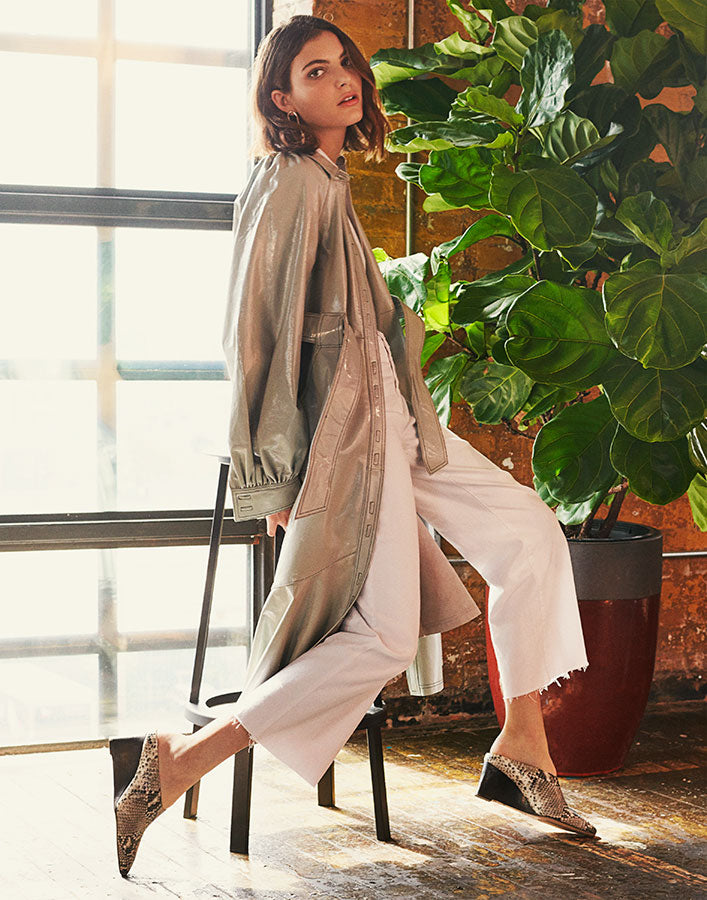 Model wears light grey leather trench coat and white denim trousers with Inez Coletta wedge mules in natural snake emboss
