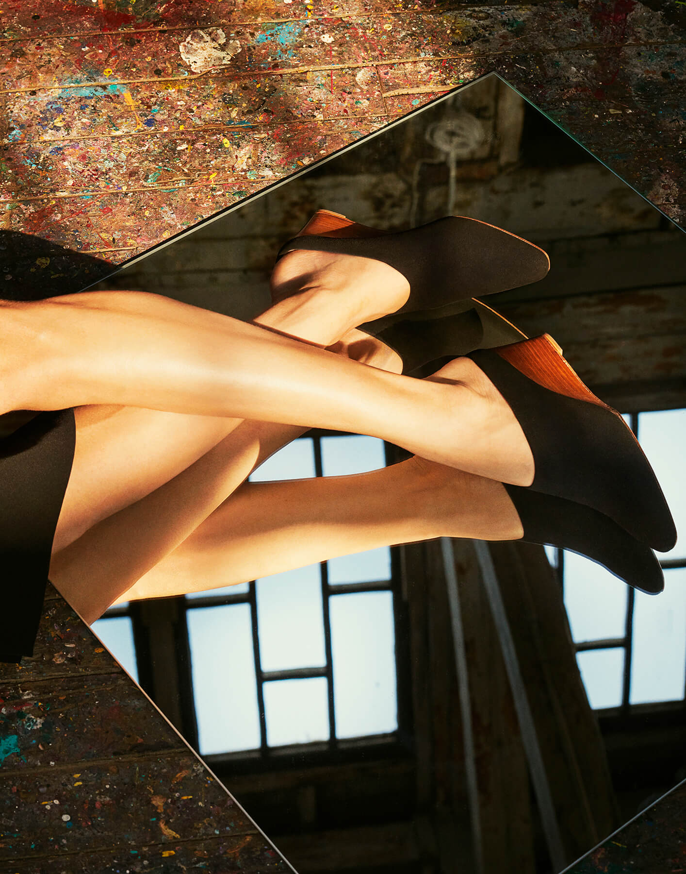 Cropped view of models legs against a mirror reflecting a skylight, wearing Inez black suede Coletta wedge mule