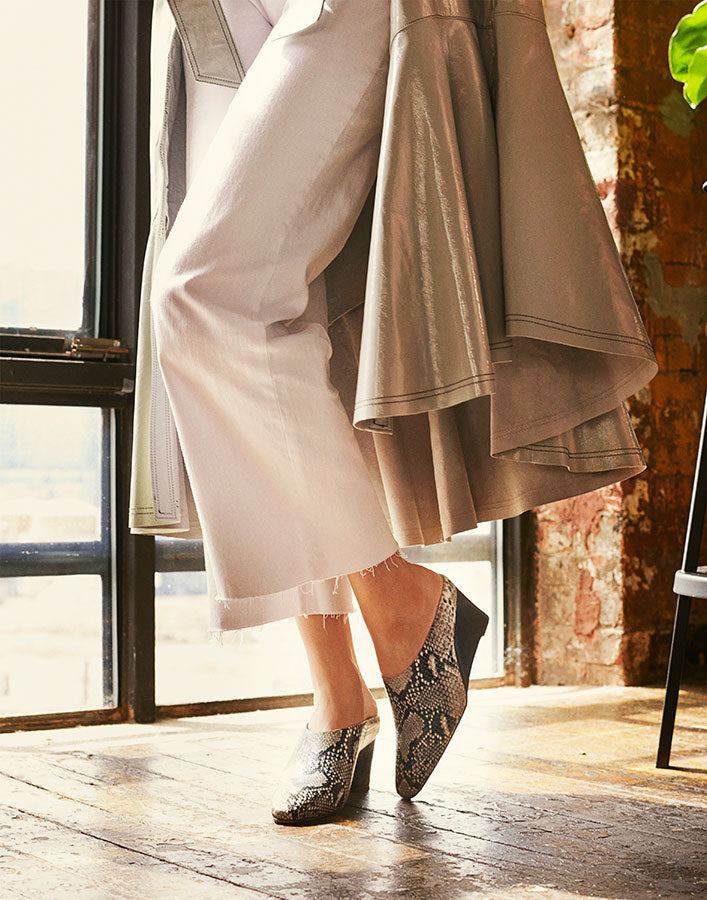 Cropped image of model standing next to sun-drenched window, wearing white denim and Inez Coletta wedge mule in natural snake emboss