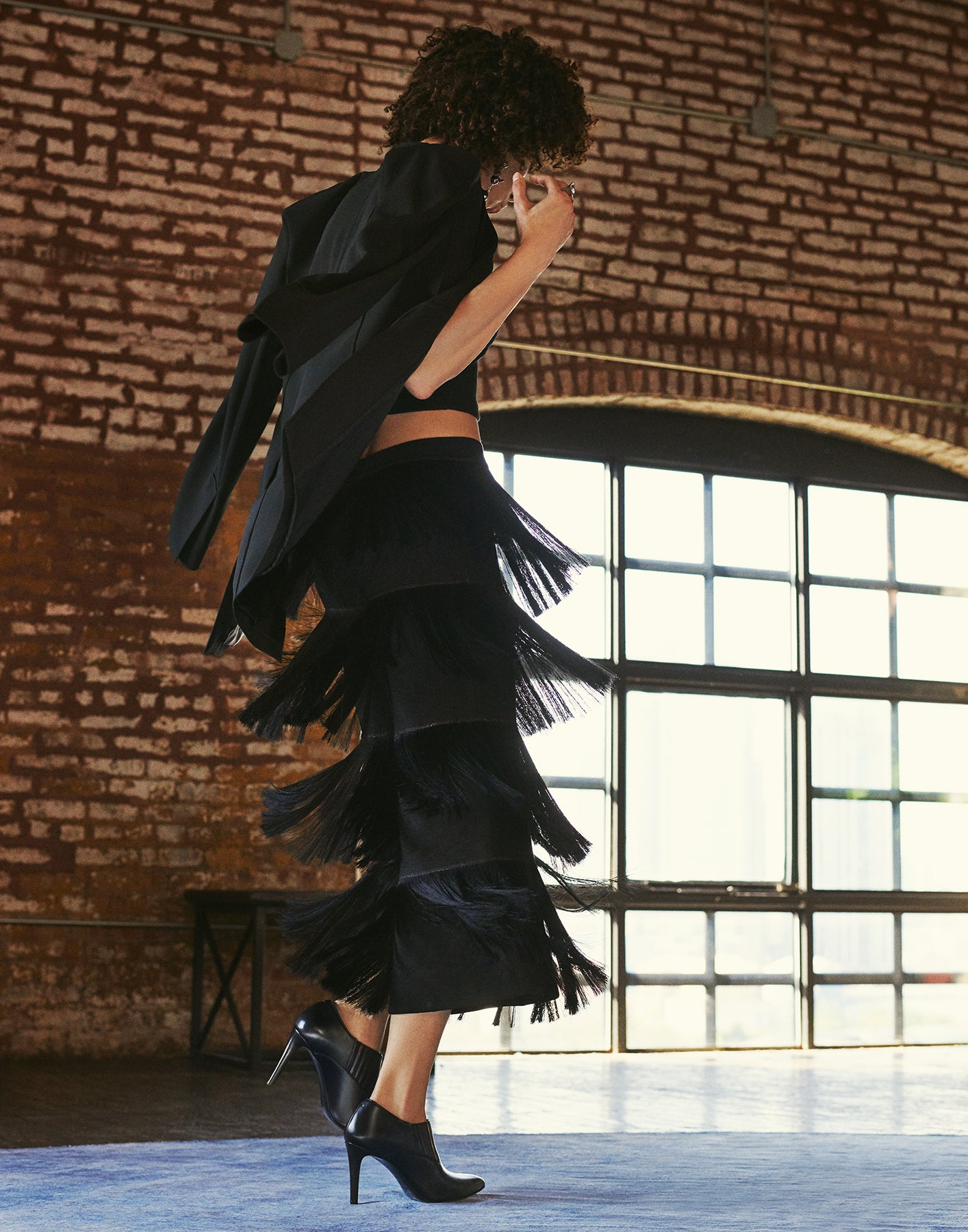 Model stepping forward in black tiered fringe pants, wearing Inez Marisol low-cut stiletto booties in black nappa