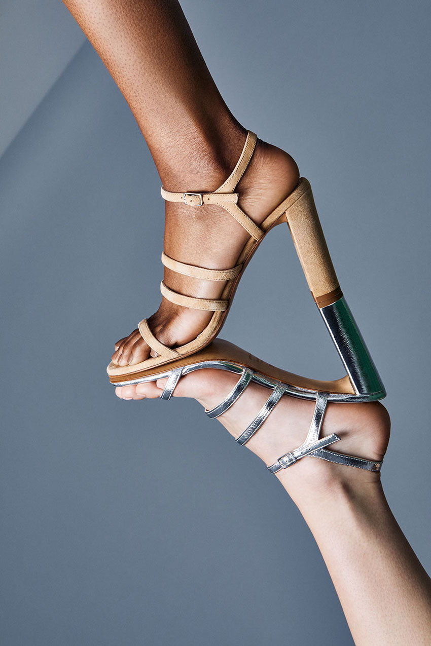 Mirrored image of two models feet pressed together at the soles, wearing Inez Sasha sandal in camel suede and silver crinkle patent