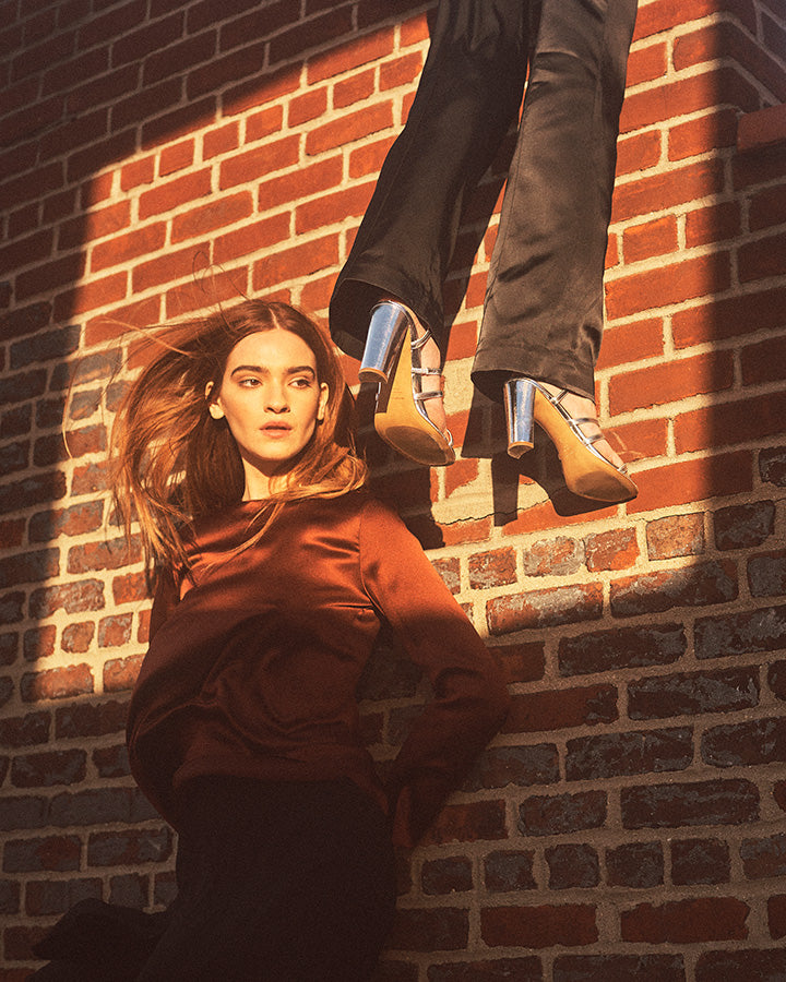 Two models against a brick wall, one with hair blowing in the wind, and the other hanging over the top of the wall wearing Inez Sasha sandal in silver crinkle patent