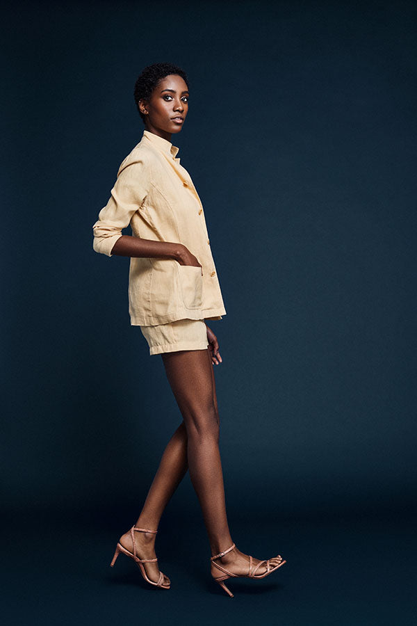 Model wearing a linen shorts suit, mid-stride with her hands in pockets, wearing Inez Sofia sandal in pink lizard emboss.