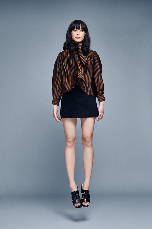 Model in black shorts and bronze and black striped silk blouse, jumping straight up in the air, appearing to levitate against a blue-grey background, wearing Inez Sol sandal in black crinkle patent.