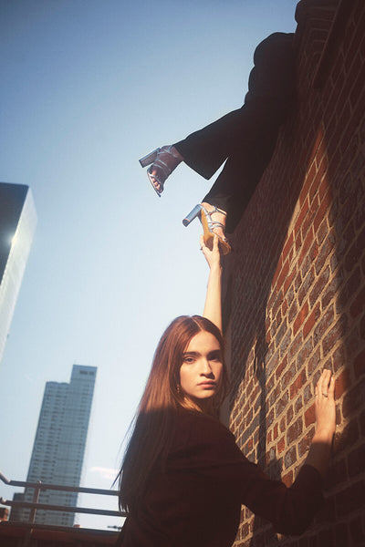 Model against city skyline reaching up to companion model's feet, hanging over a brick wall, in Inez Sasha sandal in silver crinkle patent.