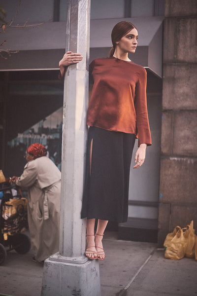 Model on city sidewalk, standing on the edge of a concrete lamppost wearing Inez Sofia sandal in pink lizard emboss.