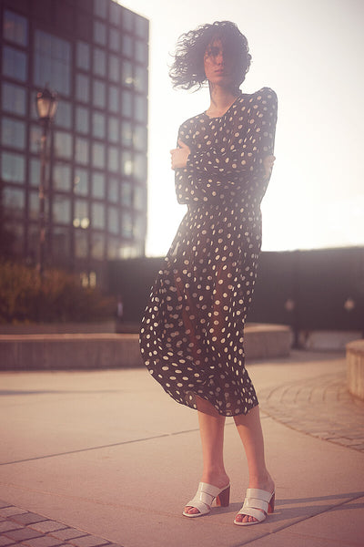 Model on windswept city landscape wearing polka dot dress and Inez Sol sandal in chalk nappa.