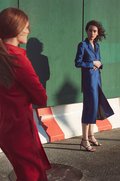Two models standing on a city sidewalk against a deep green construction barrier, on wearing a blue silk coat with Inez Sofia sandal in black crinkle patent, and the other wearing a bright red jacket.
