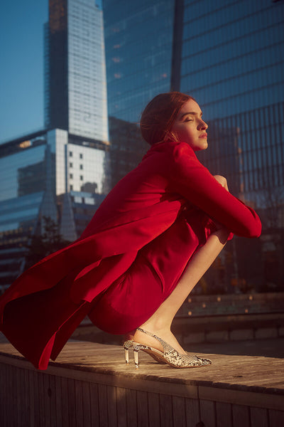 Model wearing bright red jacket and Inez Mia slingback heels in snake, crouched against background of glass city towers, with eyes closed, basking in the sunlight.