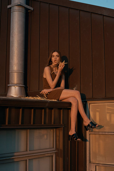 Model in sunset lighting, relaxed and sitting on a rooftop ledge eating french fries, wearing Inez Sol sandal in black crinkle patent and a tan tank dress.