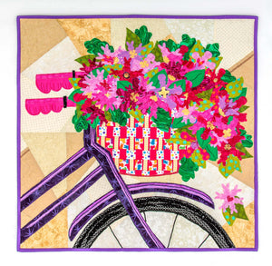 Quilt sqare depicting the front of a bike with a basket containing flowers. These flowers, and parts of the basket, are shaped like marshmallow Peeps.