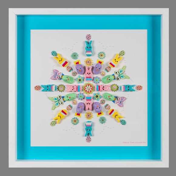 Blue, yellow, green, pink, and purple marshmallow Peeps—both rabbits and chicks—arranged in a symmetrical snowflake-like pattern atop a white square mount. Decorative eggs, flowers, and butterflies are also part of the pattern. Background behind the piece is blue, with a white frame holding everything.