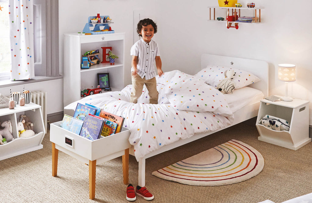 White single bed with rainbow stardust duvet cover in children's bedroom