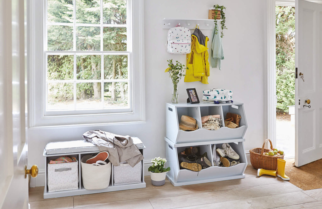 white hallway with grey stacking storage trunks and grey cube storage bench