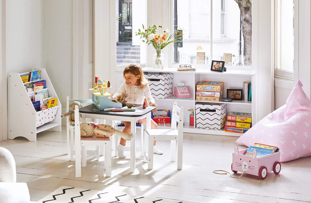 Toddler table and white cube storage in monochrome playroom