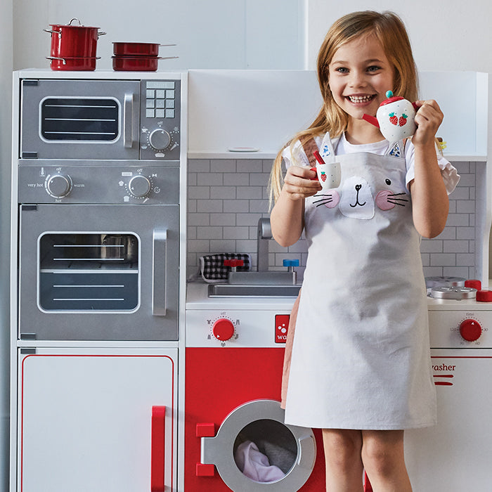 Young girl wearing cat print apron and standing in front of wooden toy kitchen set. She is making a pretend cup of tea.