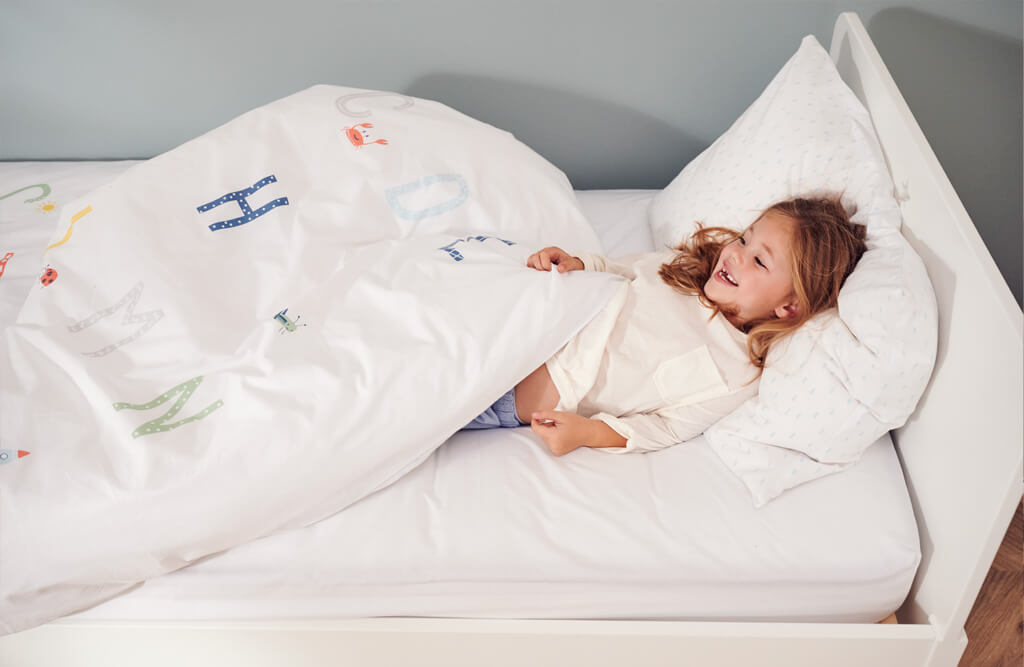 young girl layed in alphabet themed bedding