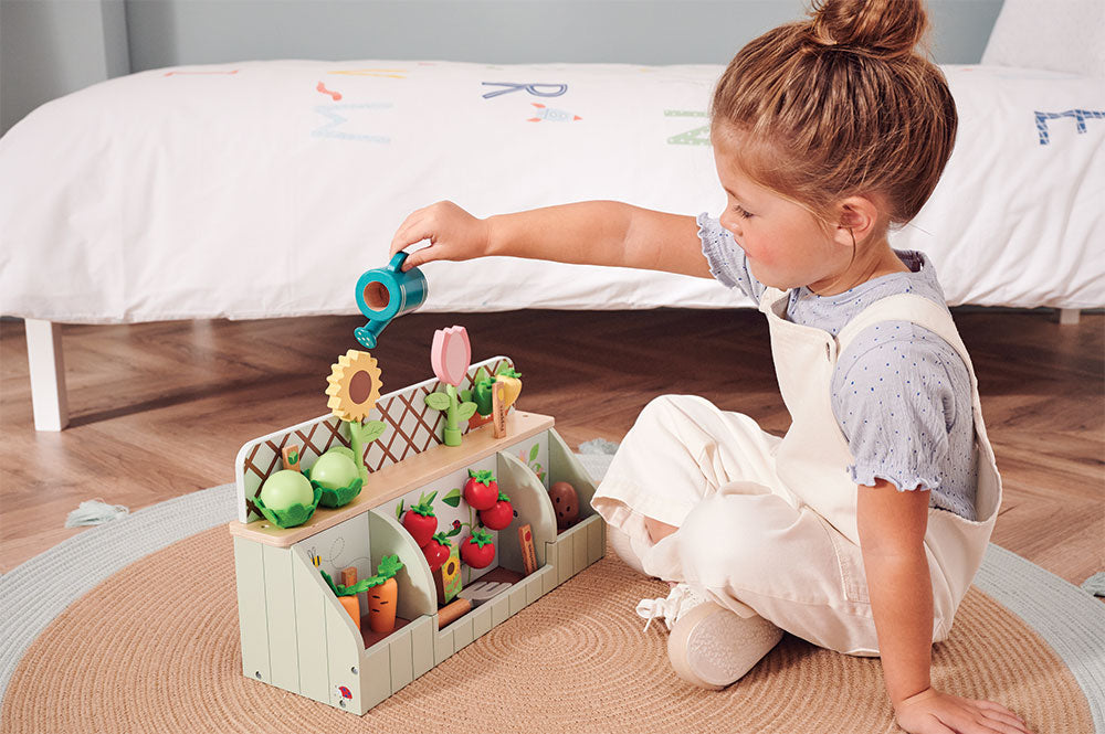 Young girl playing with wooden garden toy