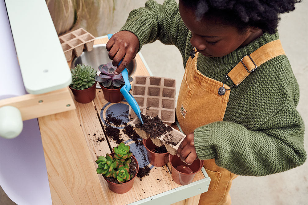 Young boy playing outside, potting plants