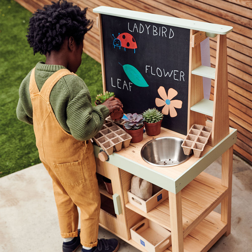 Young boy playing outside with wooden mud kitchen