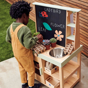 young boy playing with outdoor mud kitchen