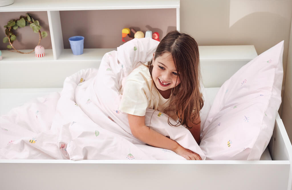 young girl wrapped in Buzzy Blooms themed duvet
