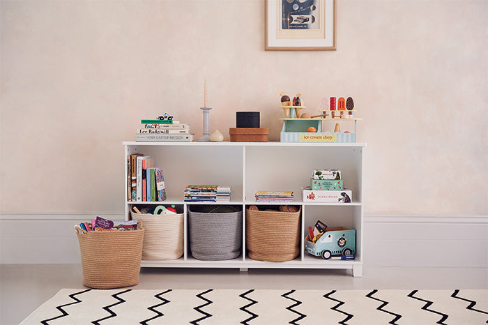 Long storage shelf filled with toys and rope storage baskets