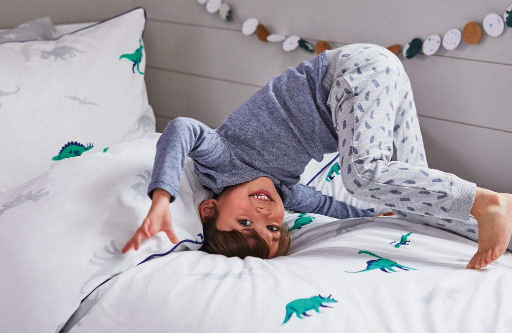Dinosaur bedding with a boy playing