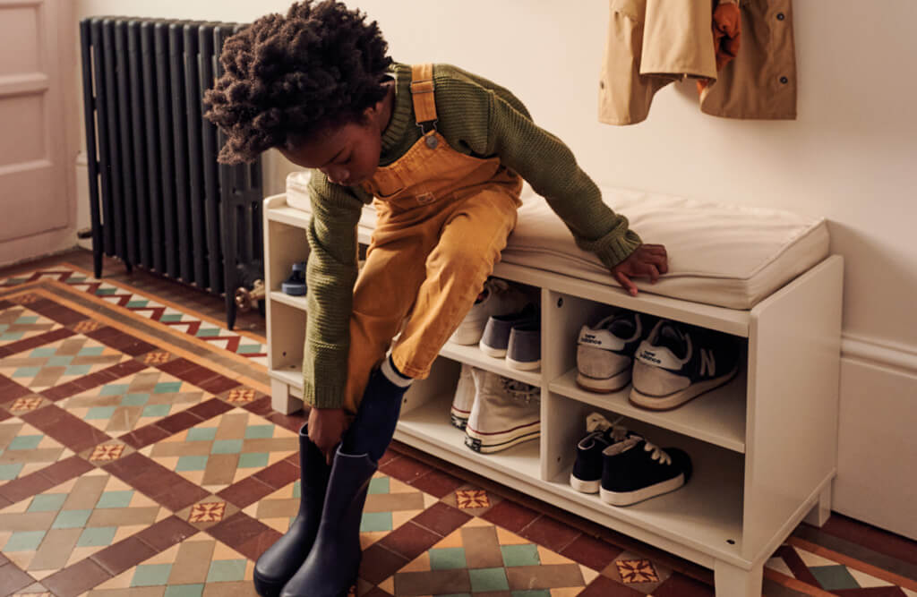 Young boy putting on shoes sat on Blake Storage Bench