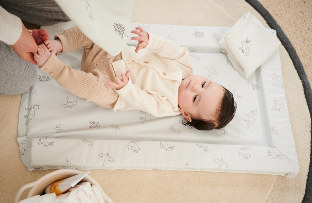 Mum playing with baby on changing mat