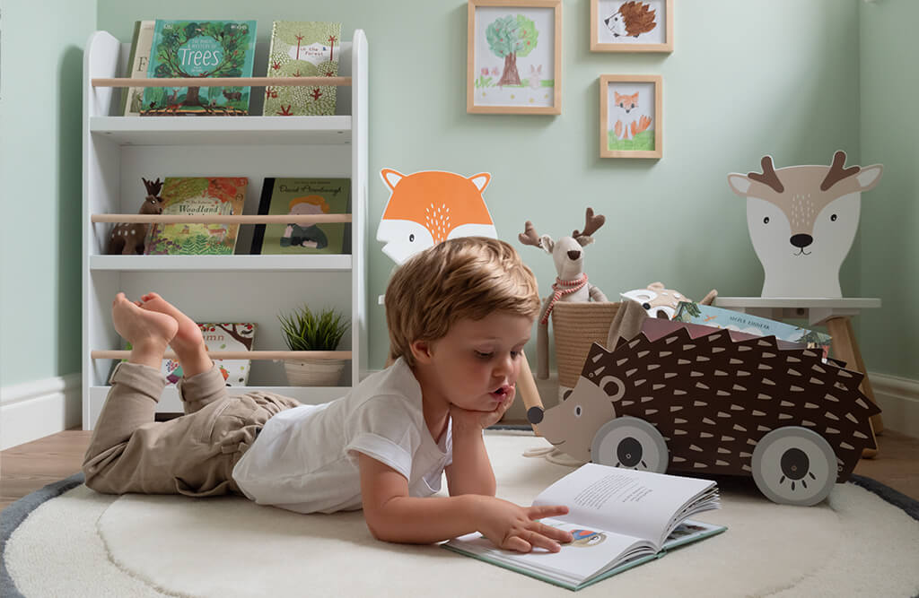 boy reading in woodland themed reading space
