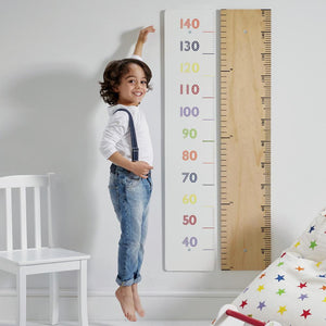 Wooden height chart in white with multicoloured numbers.