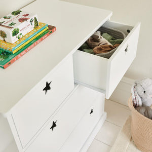 Star bright chest of drawers in white with children's books and a navy star lamp.