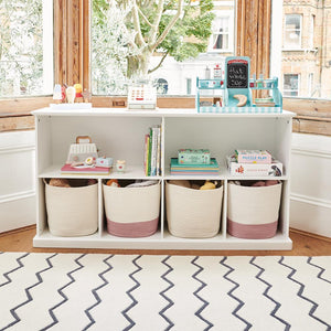 Long shelf unit in white with storage baskets, children's books and wooden toys.