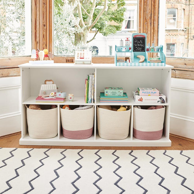 Long shelf unit in white with storage baskets and wooden toy knights.