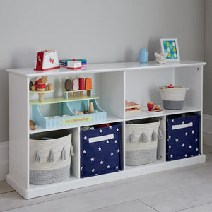 Long shelf unit in white with storage baskets and wooden toys.
