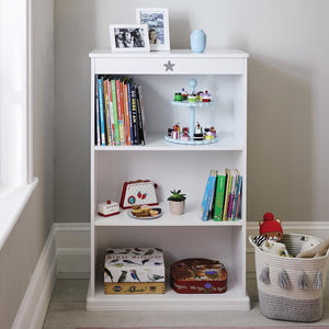 Star bright bookcase in white with children's books and wooden toys.