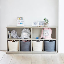 Long shelf unit in stone with storage baskets and a cuddly child's toy.