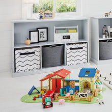 Storage shelf unit in cloud grey with wooden toys, zigzag storage cubes and grey baskets.