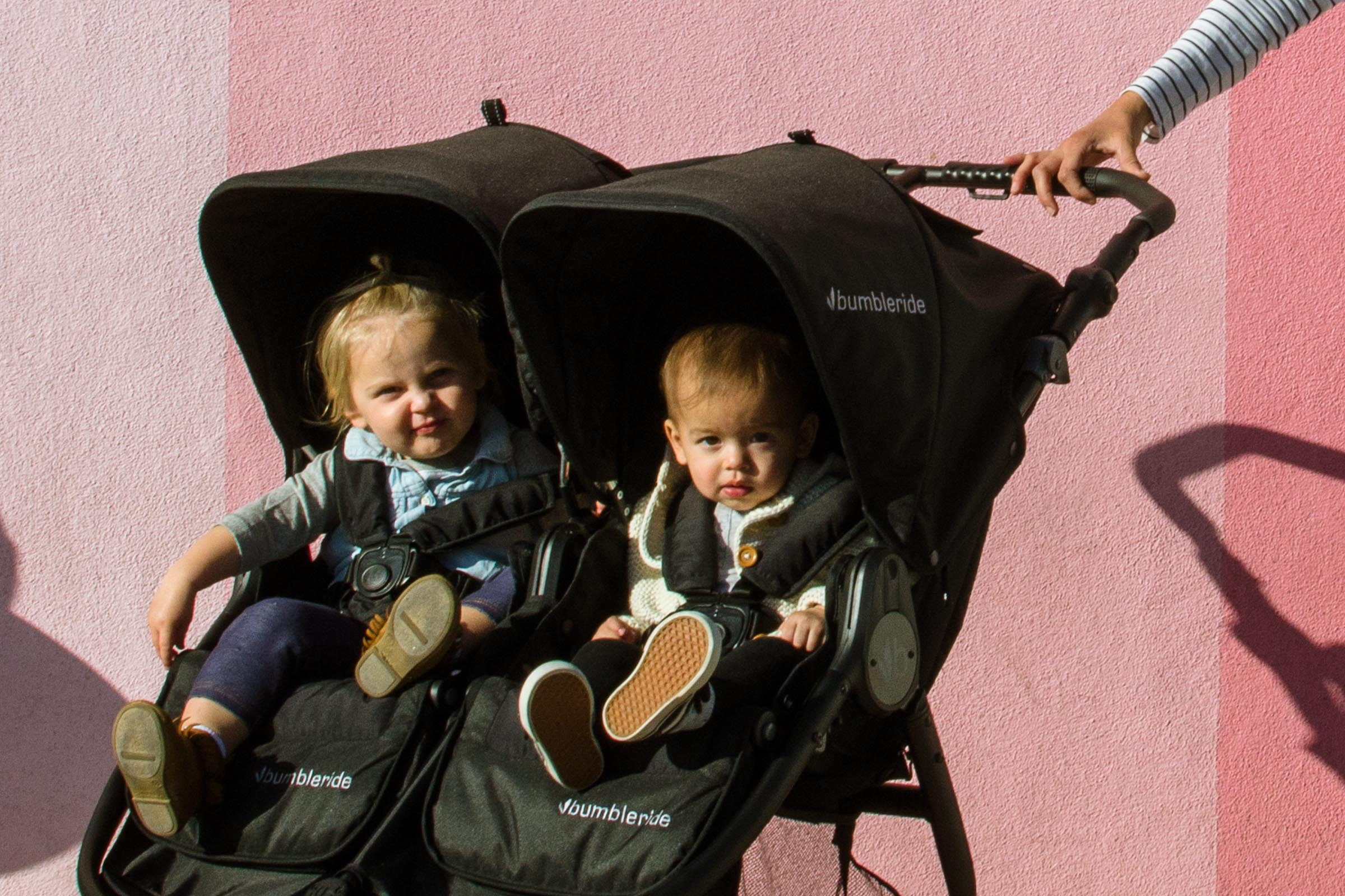 2019 Bumbleride Indie Twin Double Stroller with toddlers inside in the city - Matte Black