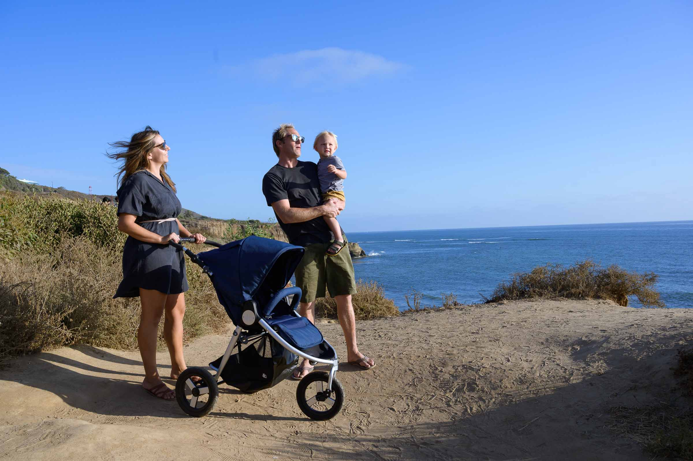 Photo of couple looking out over ocean with dad holding toddler in arms with 2021 Bumbleride Indie parked next to them on dirt