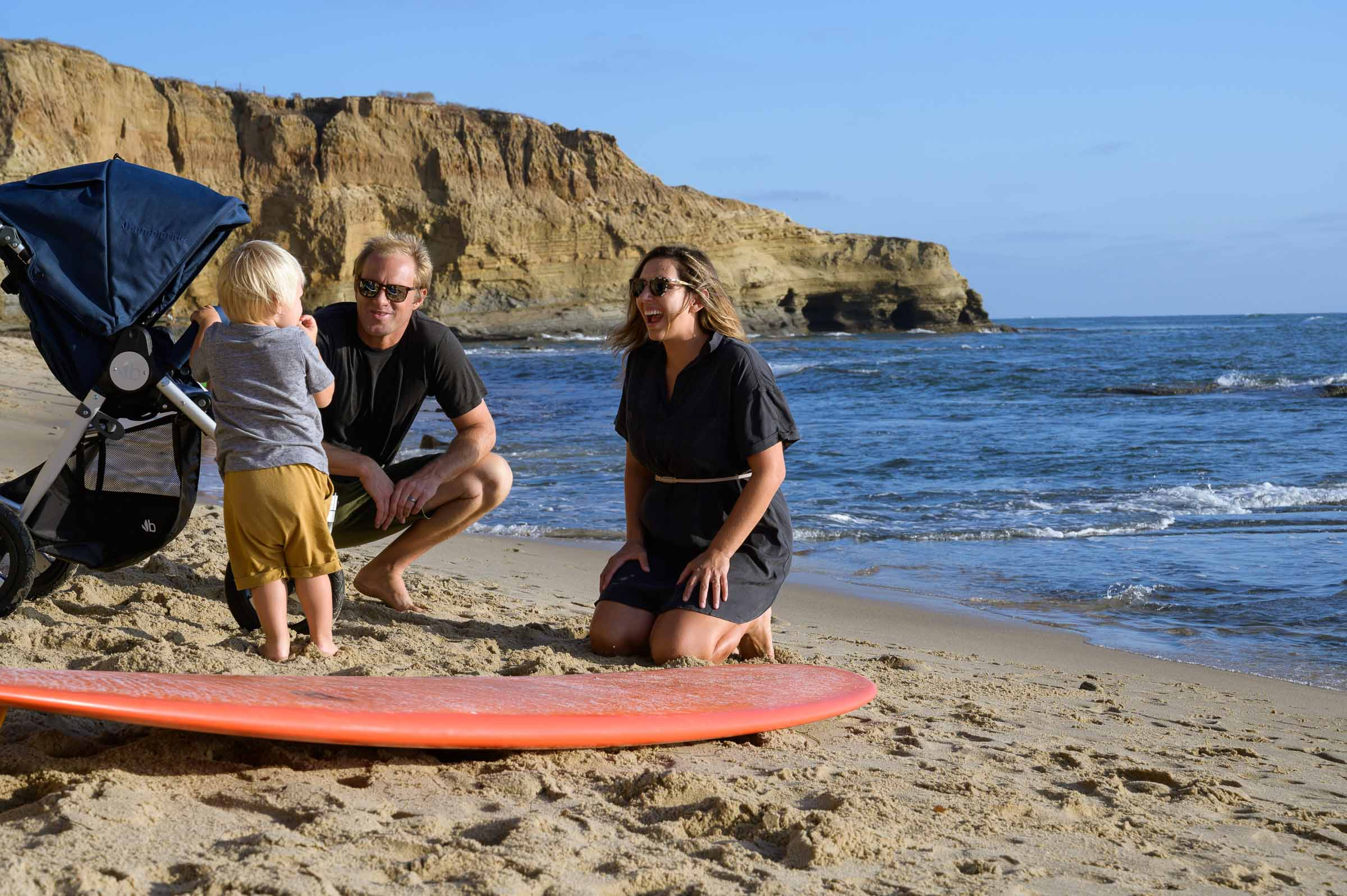 Photo of couple kneeling at beach next to toddler with their surfboard on ground with 2021 Bumbleride Indie in Maritime Blue
